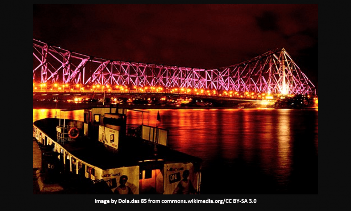 Night view of Howrah bridge with lights and reflective water